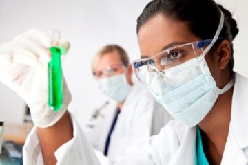 women looking at test tube in lab
