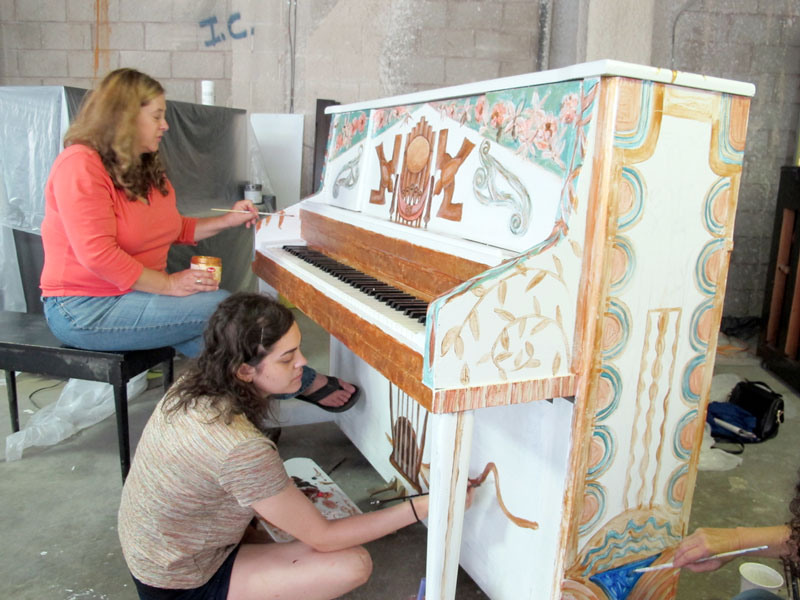 Painters work on the Cleveland Orchestra's piano.