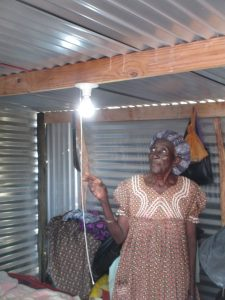 A Namibian women turns on a light in her home after solar panels were installed
