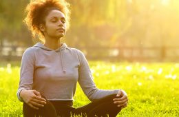 Young woman meditating in grassy area