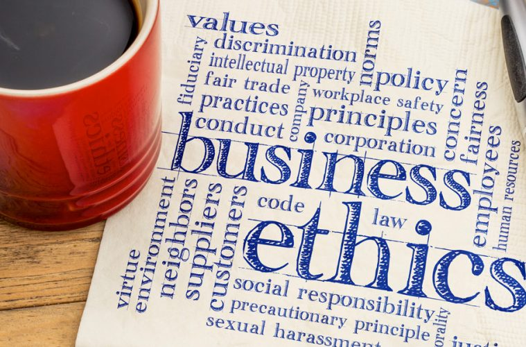 coffee cup with a napkin that has business ethics written on it