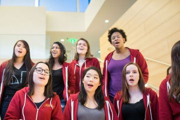 CWRU female students singing on the steps of Tinkham Veale University Center