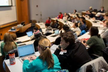 View of students in lecture hall with instructor at white board