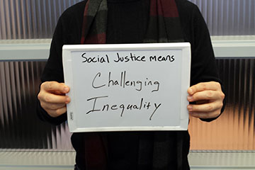 "John Flores holding sign that says ""Social justice means challenging inequality"""