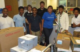 SAC school supply drop off with students and teachers behind boxes