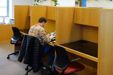 Student working at graduate student carrel at Kelvin Smith Library