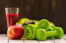 Green weights, a towel, fitness tracker, apple and smoothie gathered together
