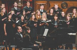 Case Concert Choir performing on stage with two pianists