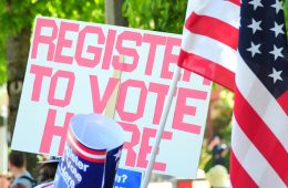 a register to vote sign at a rally with a U.S. flag in front of it
