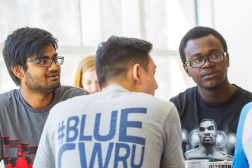 A number of CWRU students sitting around a table talking