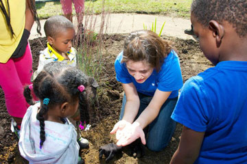 CWRU student sitting in dirt showing young children something in her hand