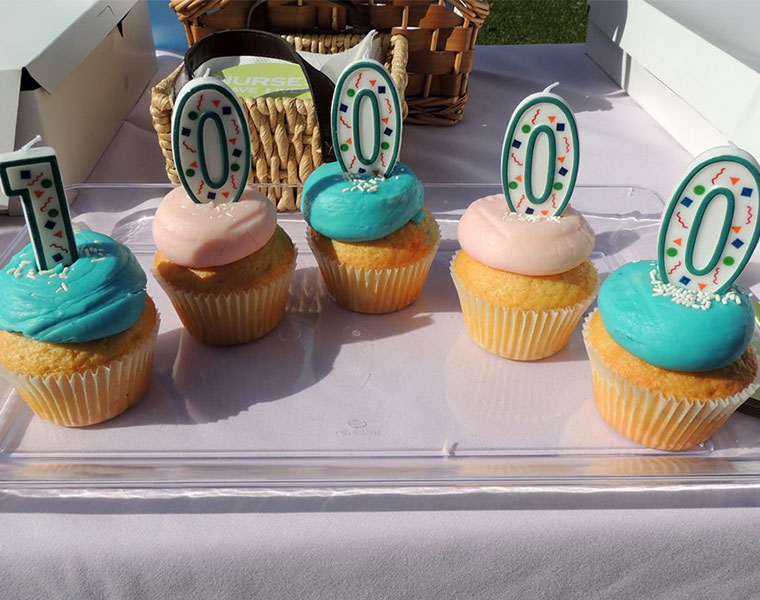"Five candles with alternating pink and blue icing with candles that write out ""10000"" on top"