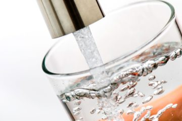 Photo of a person filling a water glass at sink