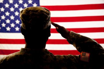 Military veteran salutes her USA flag. She wears military uniform. Patriot, honor, respect. Service to her country. Silhouette.
