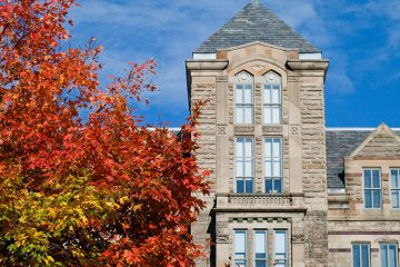 Top of Adelbert Hall's exterior with tree with red leaves in front