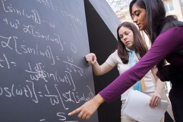 """Student points at equation written on """"Spitball"""" sculpture as instructor looks on"""