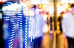 Stock market data display at outdoor with blurred people in the background