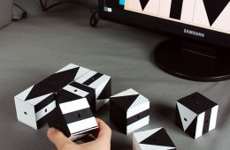 A test taker assembles blocks covered with geometric shapes to reflect an image on a computer screen.