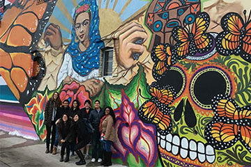 Students pose in front of mural in Detroit as part of Alternative Spring Break program