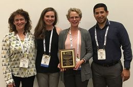 Darcy Freedman poses for photo with APHA staff members while holding award