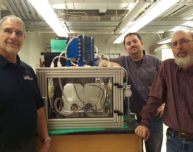 Researchers Bob Savinell, Nick Sinclair and Jesse Wainright stand next to a laboatory workbench, on which sits a 100-watt version of their iron-flow battery.