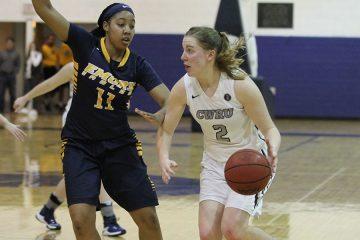 Kara Hageman dribbles basketball while opposing player tries to block her