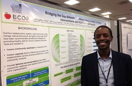 David Ngendahimana poses in front of his poster presentation