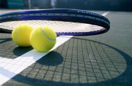Photo of two tennis balls and a racket sitting on court