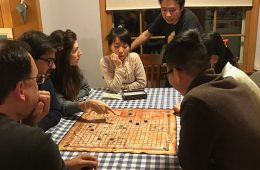 International students and host family play board game around table