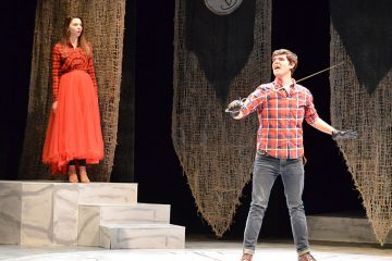 Sara Young stands on staircase and Tony Monczewski hold sword on stage