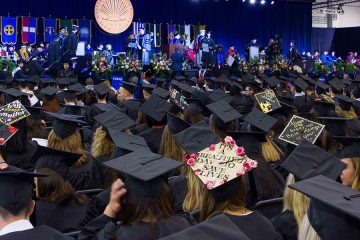 Photo of stage and tops of graduates' caps at the 2016 commencement ceremony