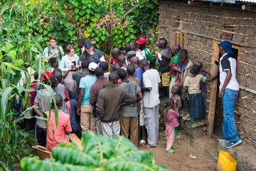 Rwandan villagers gather around engineering students