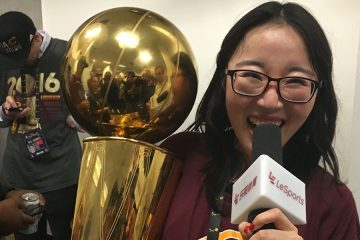 Photo of Ann Xing holding Cavs championship trophy in one hand and microphone in the other