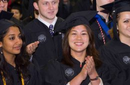 Graduates smile and applaud at commencement ceremonies