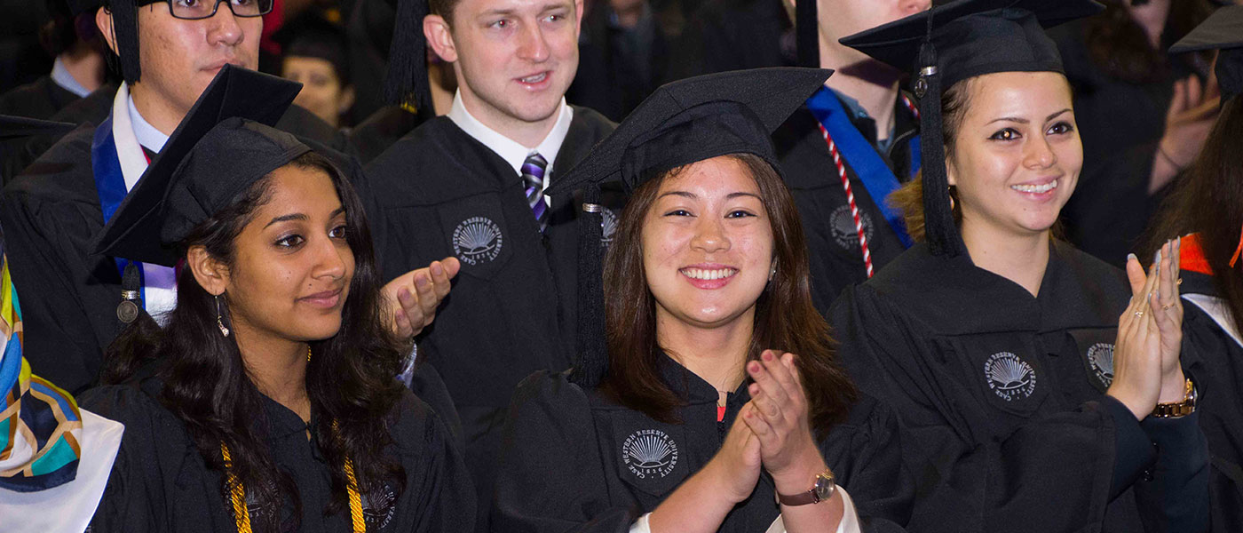 Graduates smile and applaud at commencement ceremonies