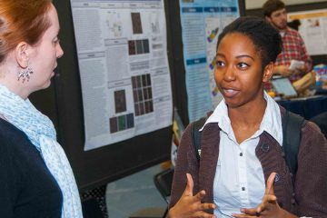 Woman talks to another in front of poster presentation at Research ShowCASE