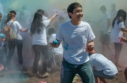Students throw colored powder at each other during Holi celebration