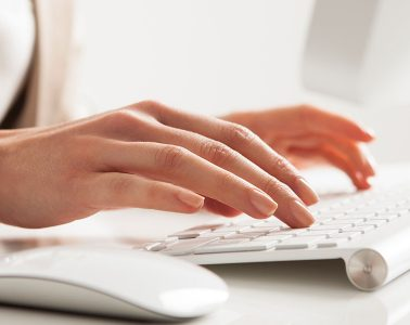 Closeup of a woman's hands typing on a keyboard