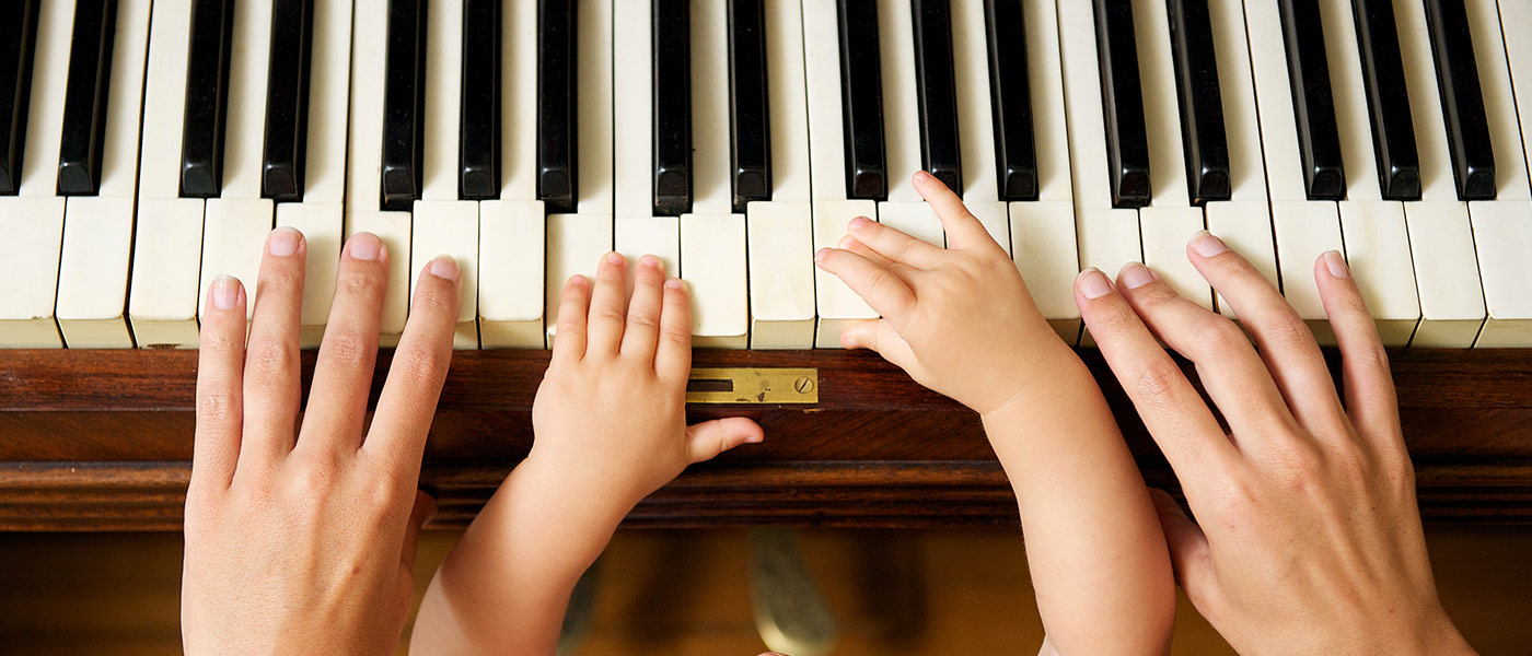 Adult and child's hands on a piano
