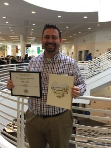Photo of Brian Gray holding certificate