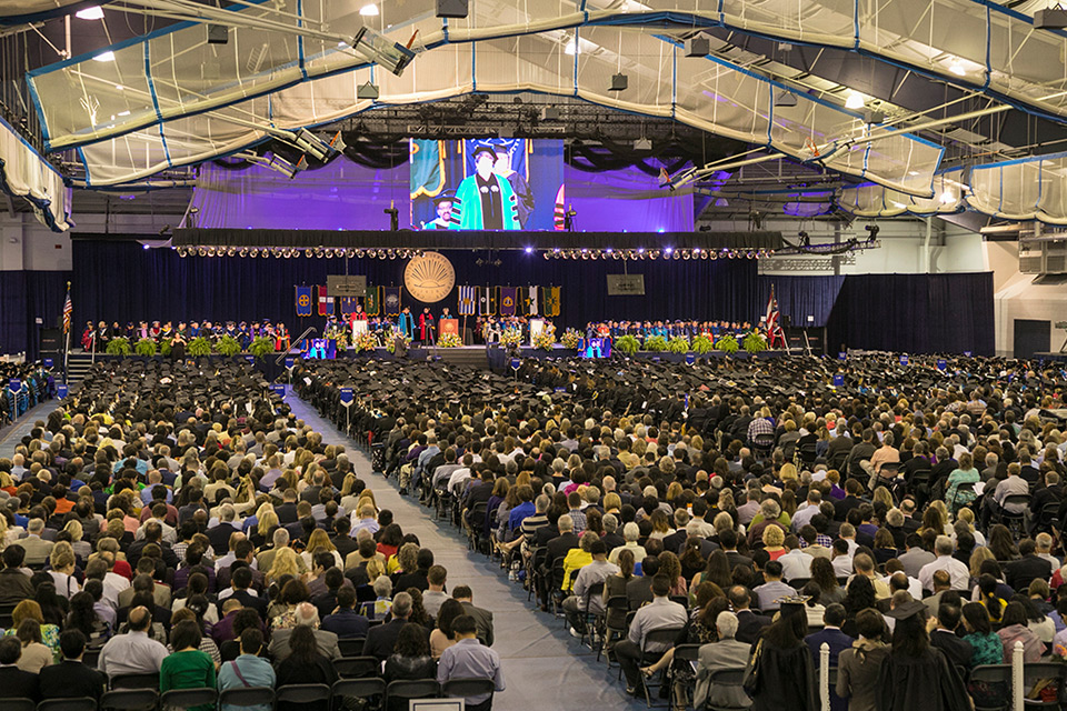 View of the audience and stage at 2017 commencement in Veale Center