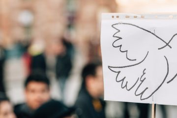 Dove drawn on piece of paper held up in above large group of people