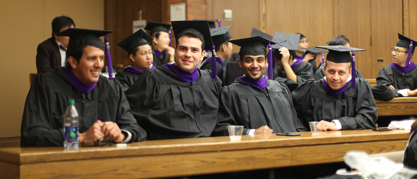 School of Law graduates in caps and gowns sitting in row at table