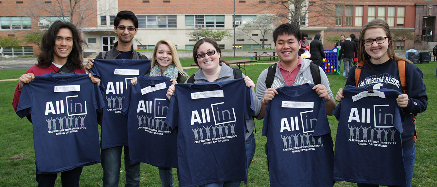 "Students holding up shirts that say ""All In"""
