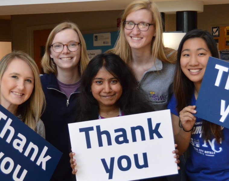 """Five female CWRU students hold signs that say """"thank you"""""""