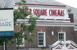 """Photo of Shaker Square Cinemas with """"Shaker Square"""" sign in foreground"""