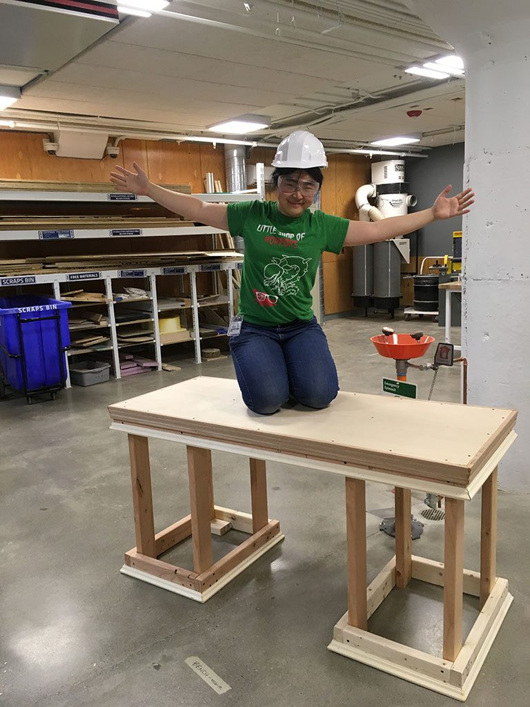 Alice Li kneels on desk she built at Sears think[box]