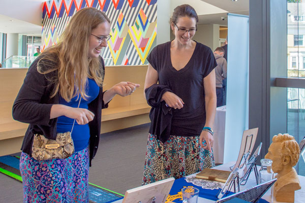 Photo of to conference volunteers discussing 3-D-printed items.