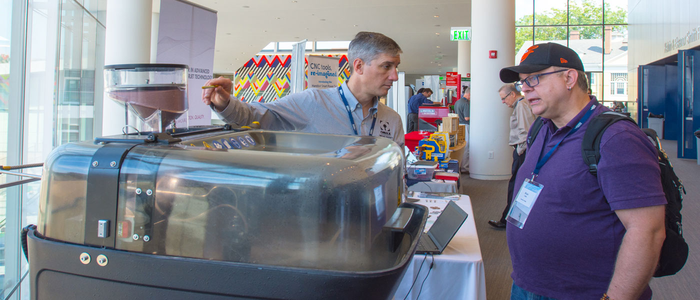 Photo of a conference vendor demonstrating a waterjet cutter.