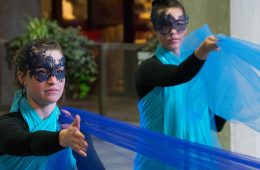 Two women perform a dance using blue fabric during Blue Block Party